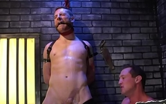 Restrained sexy gay jock in bdsm dungeon