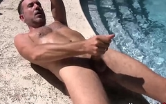 Lusty butt pirate plays with his dick by the pool and cums